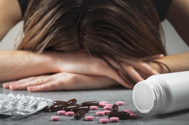 薬物乱用の概念。薬と処方薬の前のテーブルに頭を抱えた女性、うつ病または自殺の概念