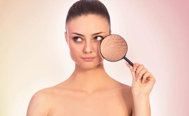 건조 손상되거나 건강한 피부, 피부 관리, 주름, 피부 문제의 개념. 그녀의 얼굴 옆에 돋보기를 들고 어린 소녀.