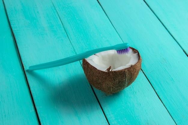 歯科医療のための環境に優しい製品のコンセプト。青い木製の背景に歯ブラシと半分のココナッツ