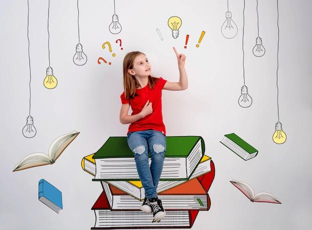 塗られた本に座っている子供女性の教育と創造性の精神の概念