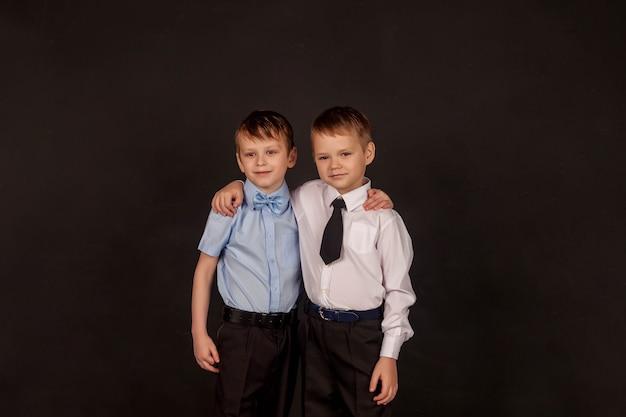 教育、育成、男性の友情と友愛の概念。黒の背景に、抱き合って幸せな2人の小さなスタイリッシュな男の子の兄弟と友人。同じ目標に向かって2人の男の肖像