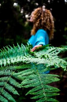 環境の概念と背景の熱帯の緑の葉と女性のクローズアップで地球を救う-人々のための自然と屋外の森林ケアは屋外を愛しています