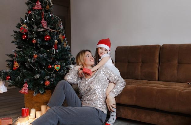 가족, 크리스마스, 휴일 및 사람들-행복한 어머니와 집에 소파에 앉아 작은 딸의 개념