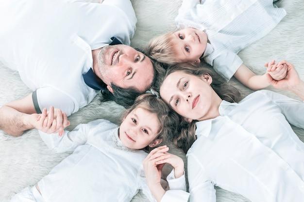 Концепция семейного счастья счастливая семья отдыхает на ковре в воскресенье