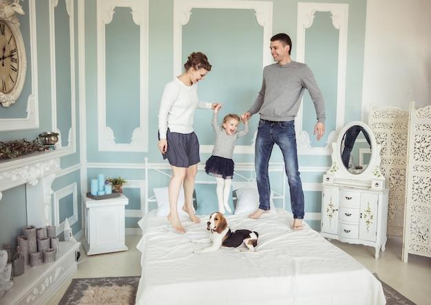 가족 행복의 개념 : 침실에서 침대에 아기 딸과 함께 노는 사랑하는 부모