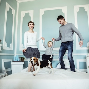 침실에서 침대에 아기 딸과 함께 노는 가족 행복 사랑 부모의 개념