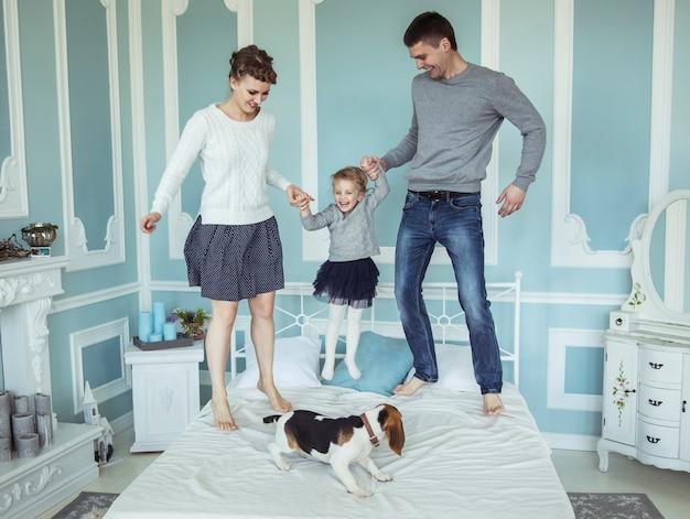 寝室のベッドで赤ん坊の娘と遊んでいる家族の幸せを愛する両親の概念