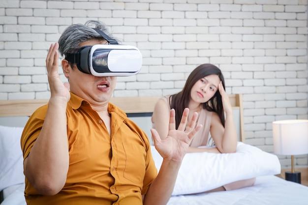 가족 문제의 개념. 노인 아시아 인 남편은 vr 게임에 매우 중독되어 있습니다. 젊은 아내는 남편이 그녀에게 관심이 없다는 것을 지루하게 만듭니다.