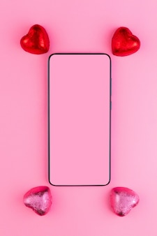 2月14日またはバレンタインデーのコンセプト。赤とピンクのラッパーのチョコレート菓子のハートは、スマートフォンの近くにあります。モックアップ。