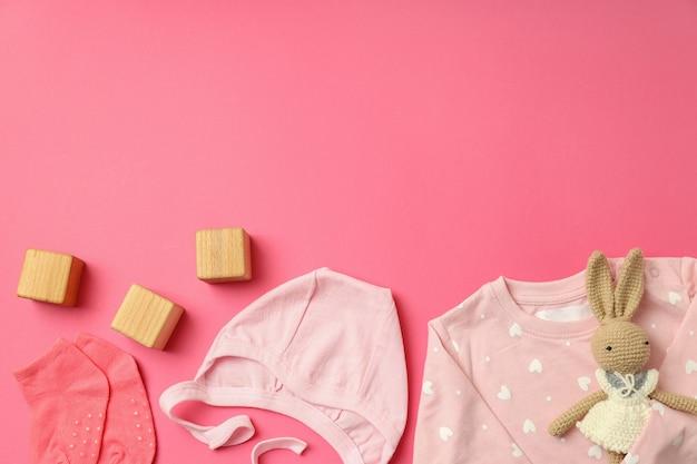 Концепция женской детской одежды на розовом фоне.