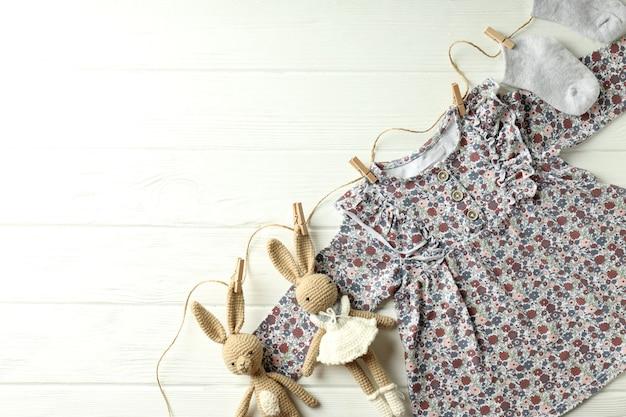 Концепция женской детской одежды на белом фоне деревянных.