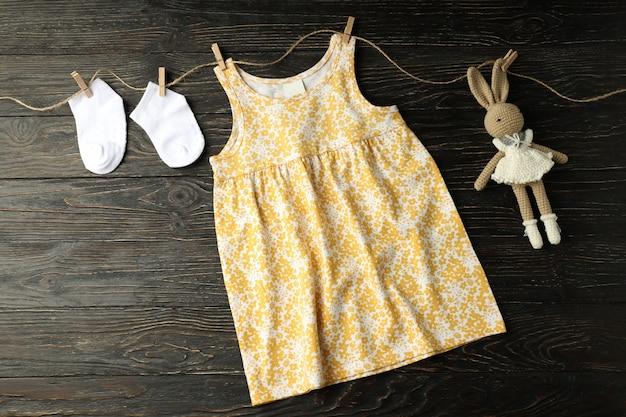 Концепция женской детской одежды на деревянных фоне.