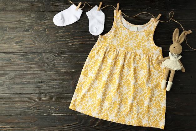 木製の背景に女性の赤ちゃんの服の概念。