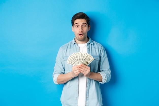 金融、クレジット、銀行の概念。お金を持って、カメラを見て驚いた男は、青い背景の上に立って不思議に思った