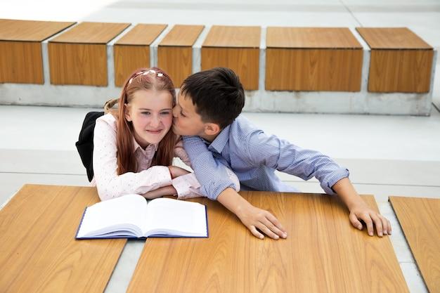 最初の気持ち、最初のキス、学校の愛の概念。男の子は女の子にキスします、ティーンエイジャーはとても幸せで驚いています、子供時代、学校生活、ライフスタイル