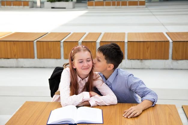 最初の気持ち、最初のキス、学校の愛の概念。男の子は女の子にキスします、ティーンエイジャーはとても幸せで驚いています、子供時代、学校生活