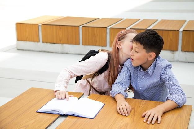 最初の気持ち、最初のキス、学校の愛の概念。女の子は男の子にキスします、ティーンエイジャーはとても幸せで驚いています、子供時代