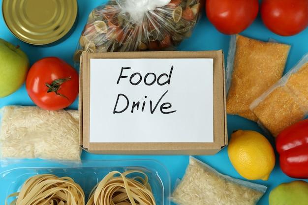 青い背景の上の食事とフードドライブの概念