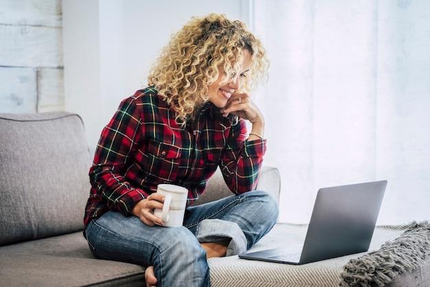 自由で幸せな人々の概念は、オフィスではなく自宅でコンピューター技術を使用しています-ラップトップを持った陽気な白人女性が、背景に窓のあるソファに座っています