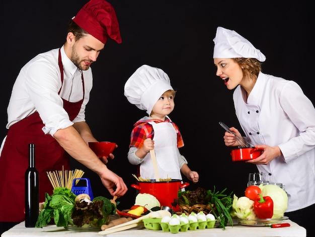 キッチンでフレンドリーな家族の幸せな家族の概念シェフの帽子で家の愛らしい子供で健康的な食べ物