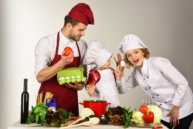 フレンドリーな家族、相互支援、サポート、料理のコンセプト-キッチンで幸せな家族。家庭での健康食品。彼女の両親と一緒にシェフの帽子をかぶった愛らしい子供。母と父は男の子に料理の仕方を教えています。