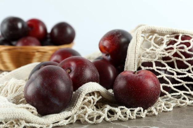 Концепция фруктов со сливами на сером текстурированном столе.