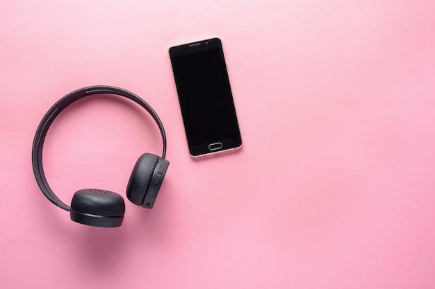 音楽愛好家のためのガジェットの概念。ワイヤレスヘッドフォンとスマートフォン