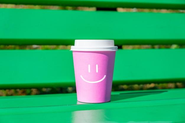 使い捨てコーヒーのカップにスマイリーフェイスで良い気分とポジティブの概念