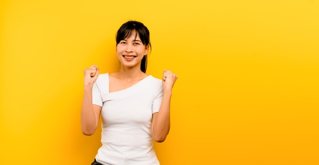 黄色の背景に一人で立って幸せなアジアの女の子の幸せの写真の概念カメラを見て、彼の拳を握り締めて、彼は幸せで笑顔です。