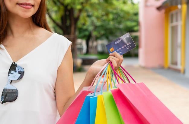 ショッピングやバッグやカード、クローズアップ画像を保持している幸せな女性の概念。