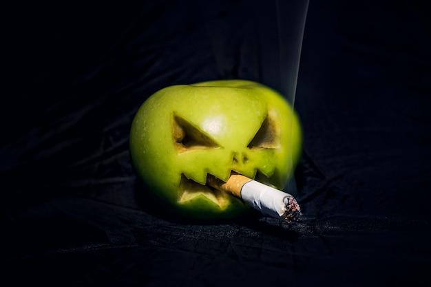 흡연으로 인한 건강에 대한 해악의 개념. 담배를 입에 물고 있는 사악한 사과.