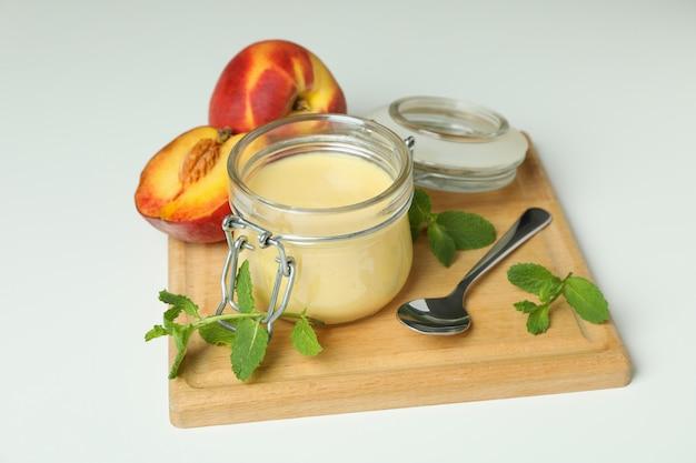 Концепция здорового питания с персиковым йогуртом на белом фоне
