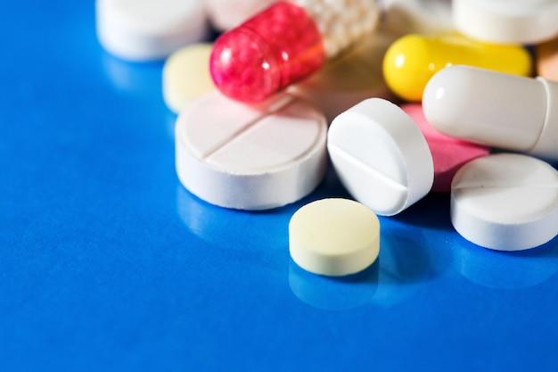 Концепция здорового образа жизни. макро цветные таблетки на синем фоне.