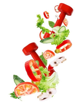 Концепция здорового образа жизни. спортивное оборудование с овощами летают, изолированные на белом фоне