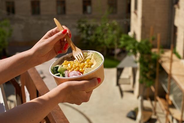 Концепция здорового веганского обеда в женских руках на улице. салат из авокадо и киноа. доставка еды, еда на вынос.