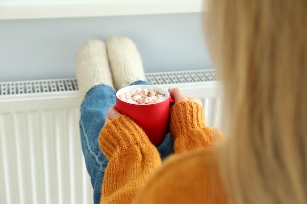ラジエーターの近くに座っている女の子と暖房の季節の概念。