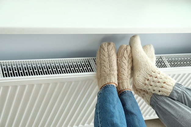 ラジエーターのニットブーツの脚で暖房シーズンの概念。