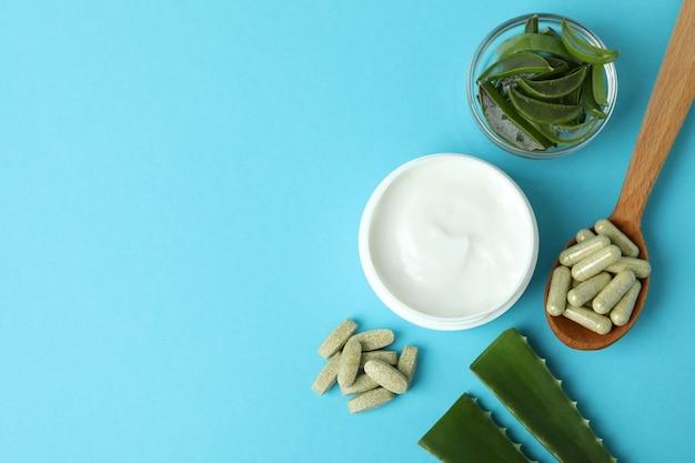 Концепция травяных таблеток и косметики с алоэ на синем фоне