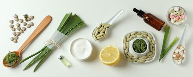 Концепция травяных таблеток и косметики с алоэ на белом фоне