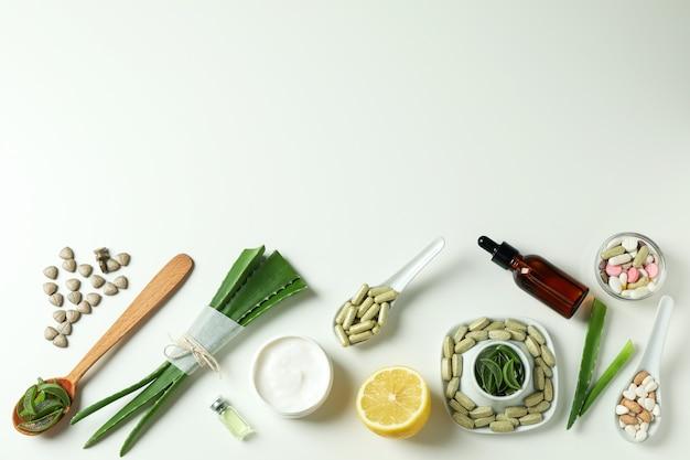 白い背景の上のアロエとハーブの丸薬や化粧品の概念