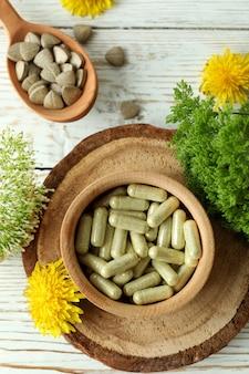 Концепция таблеток фитотерапии на белом деревянном столе, вид сверху