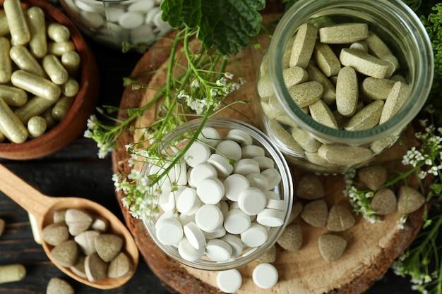 Концепция таблеток фитотерапии на деревянном столе, вид сверху