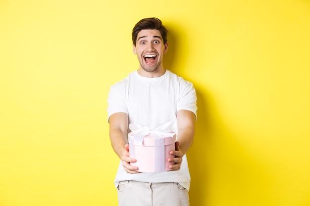 休日やお祝いの概念。黄色の背景に立って、贈り物を与えて興奮しているように見える幸せな男。