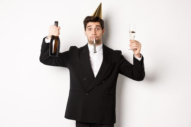 휴일 및 라이프 스타일의 개념입니다. 생일을 축하하고 파티 휘파람을 불고 샴페인을 들고 건배를 하고 흰색 배경 위에 양복을 입고 서 있는 잘생긴 남자.
