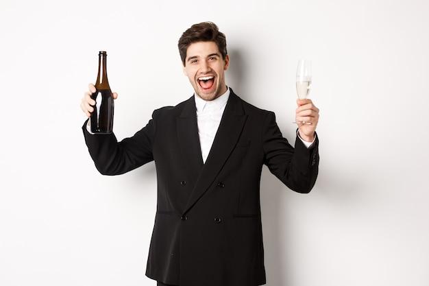 休日、パーティー、お祝いの概念。楽しんで、白い背景の上に立って、シャンパンのボトルとグラスを持って、トレンディなスーツを着たハンサムな男。