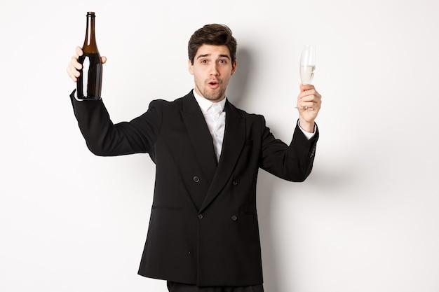 休日、パーティー、お祝いの概念。スタイリッシュなスーツを着て、シャンパンのボトルと踊り、新年に飲んで、白い背景の上に立っているハンサムな男の画像