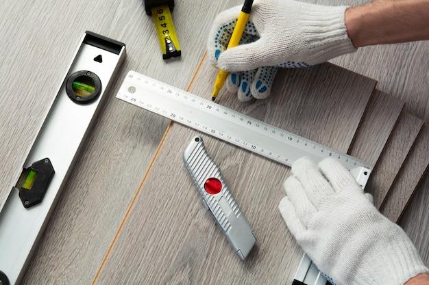 주택 개선의 개념. 남자는 새로운 라미네이트를 측정