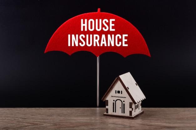 Концепция страхования дома с деревянным миниатюрным домиком