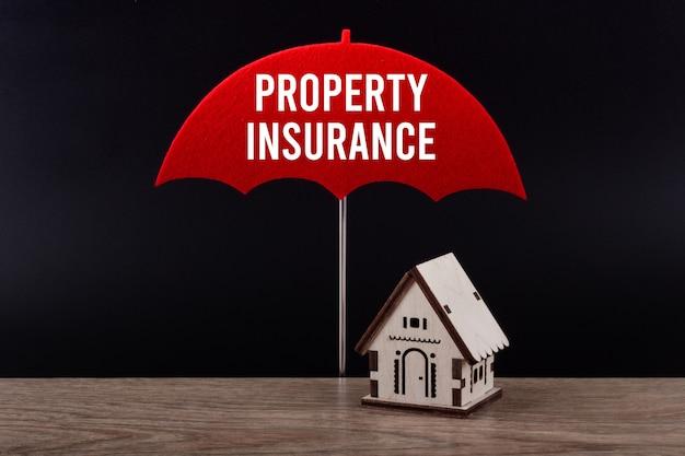 집 보험의 개념. 텍스트 속성 보험 빨간 우산 아래 목조 주택입니다.
