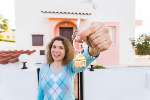 Концепция новоселья, недвижимости, собственности и переезда - новый владелец дома с ключом крупным планом
